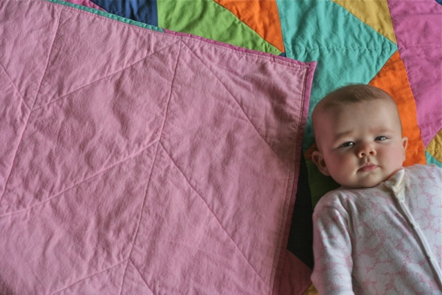 Baby with back of Triangle Quilt
